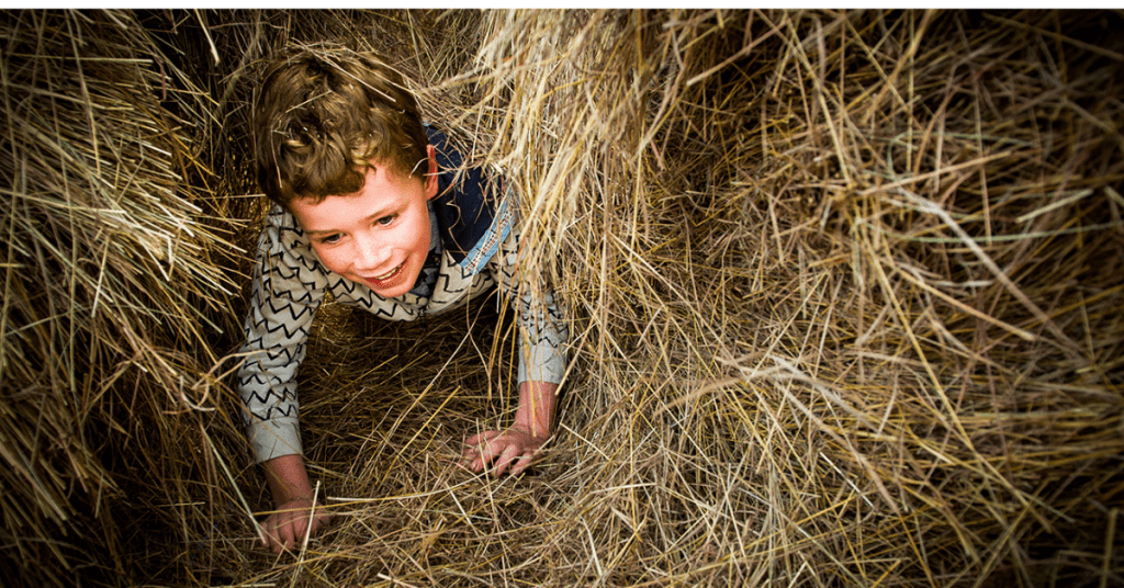 A young smiling boy wearing snug winters clothing, crawling through dry grass