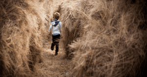 A young boy wearing snug winters clothing, running away from the camera through a field of dry grass