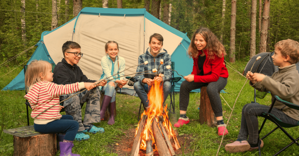 A group of children sitting around a campfire roasting marshmallows with a tent behind them